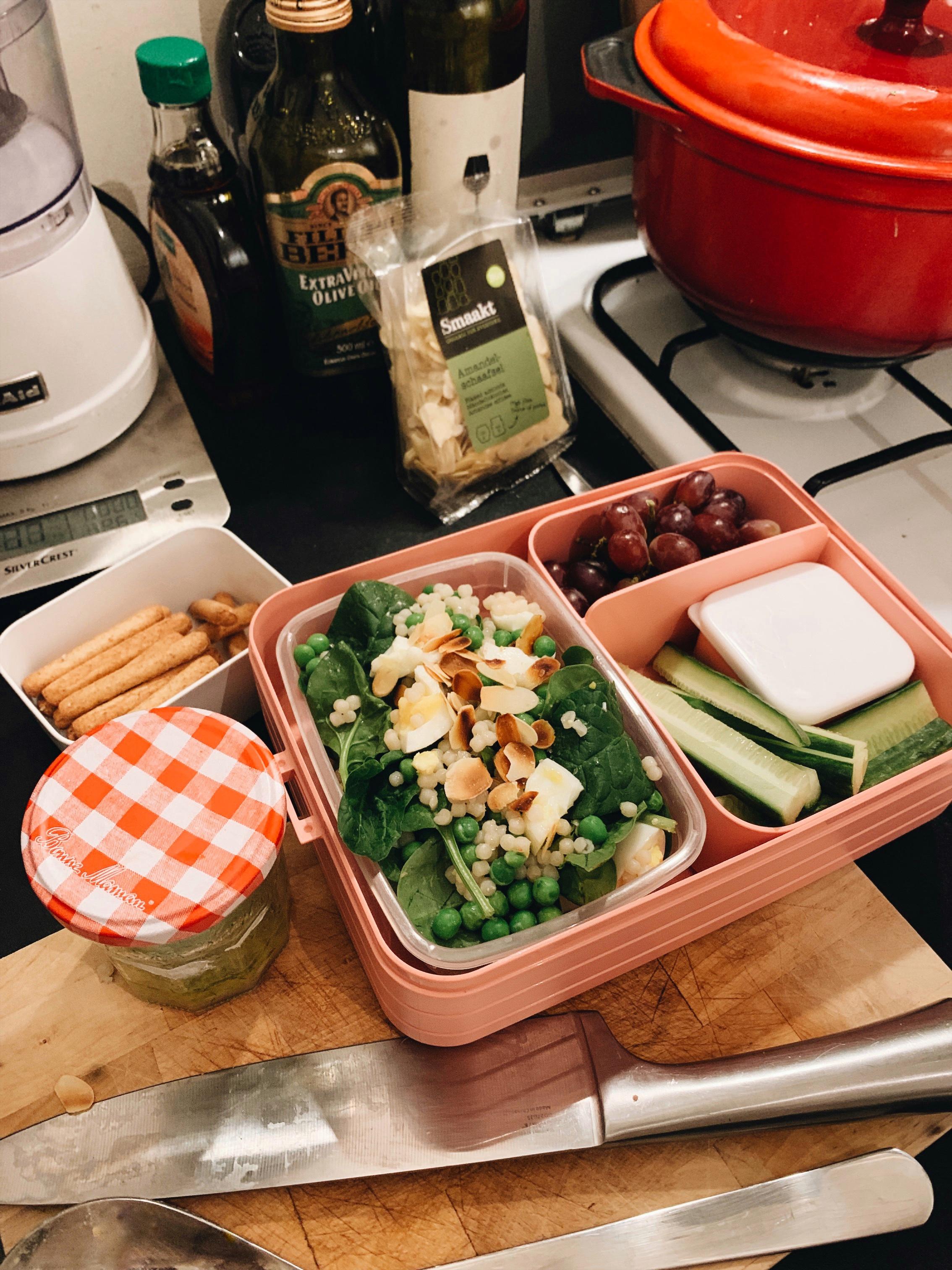 Spinazie-couscoussalade met ei, geroosterd amandelschaafsel, druiven, hummus met komkommer, mini-soepstengels en dressing in een jampotje.
