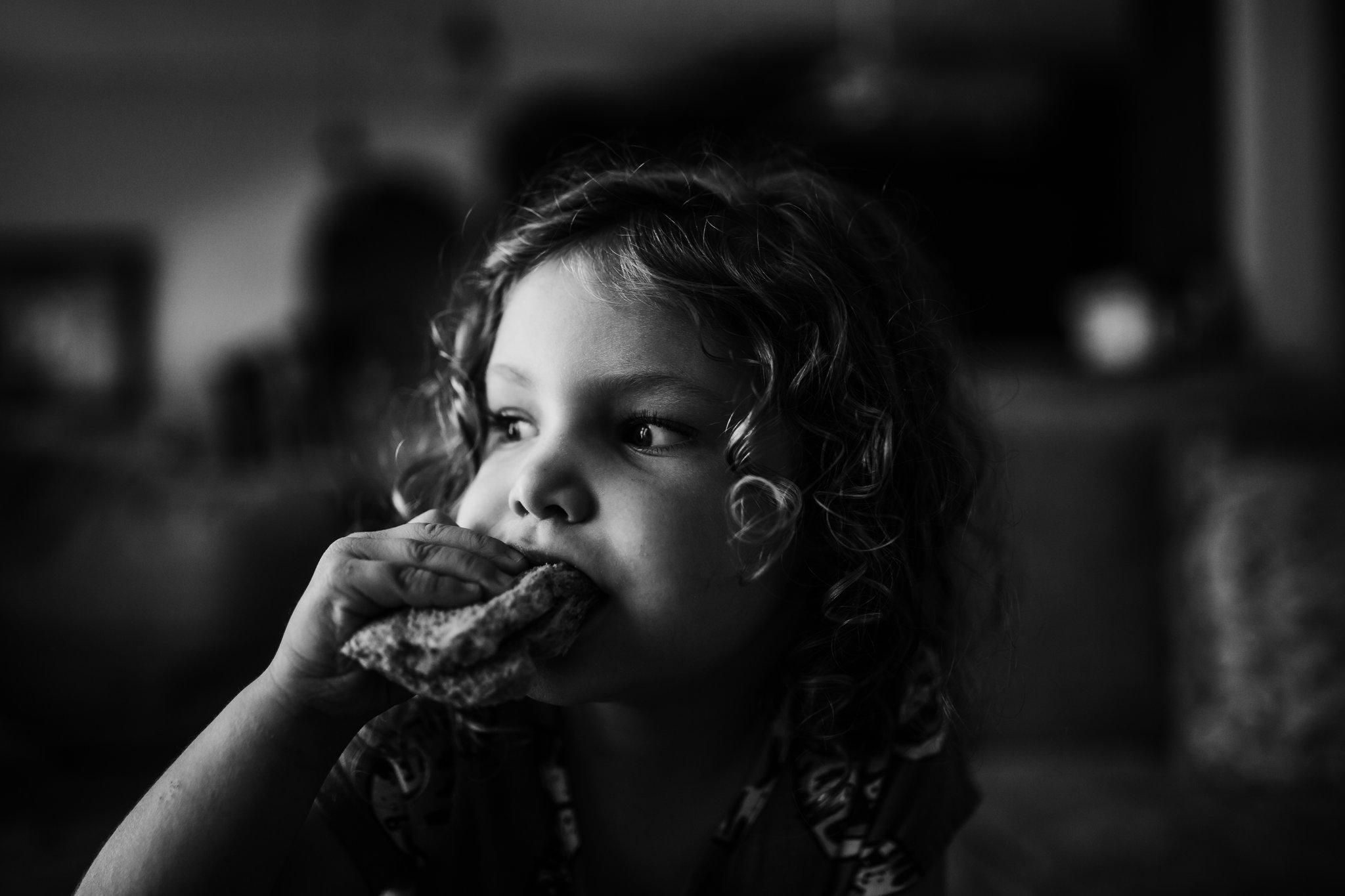 Little girl eats peanut butter and jelly sandwich
