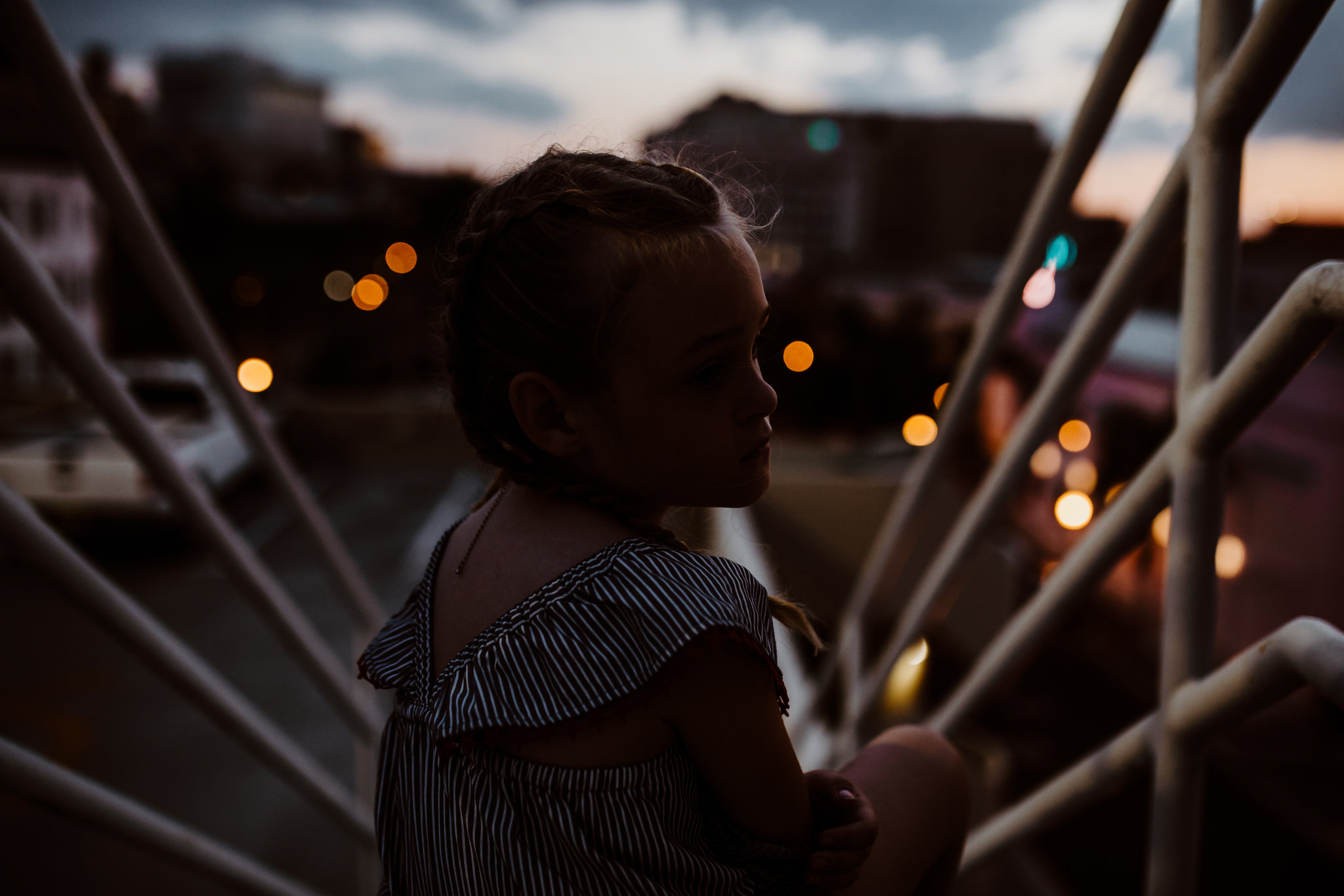 Little girl sits on stairs with downtown Fort Myers lights in background