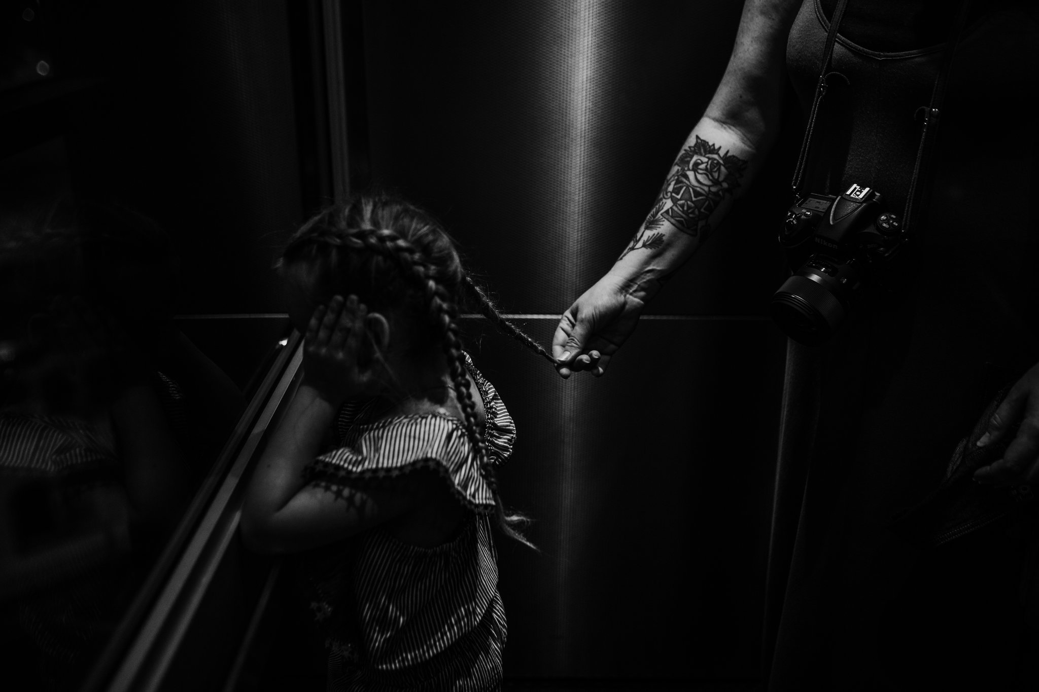 Mother plays with daughter's hair in elevator
