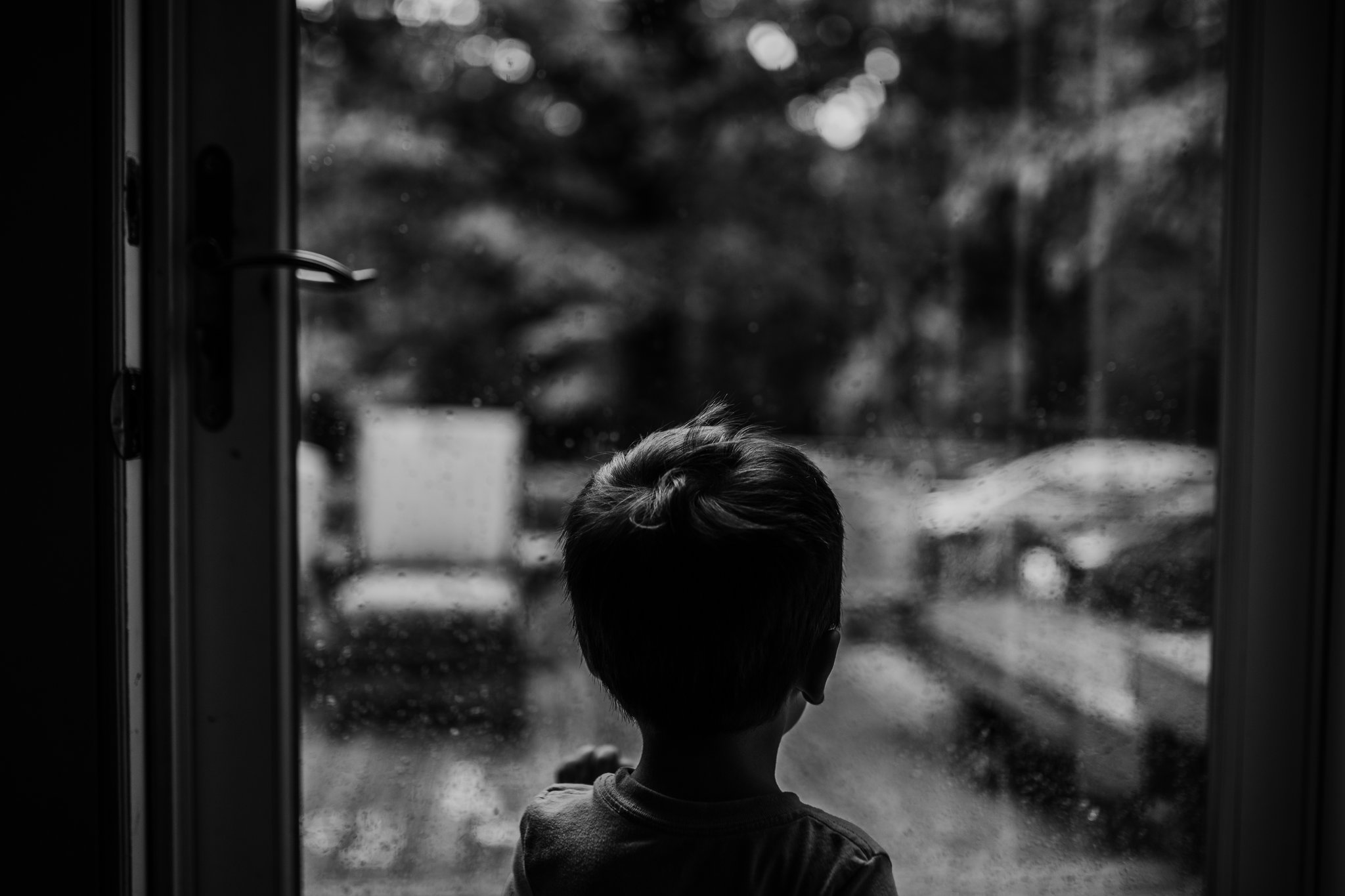 Little boy looks out front door at the rain