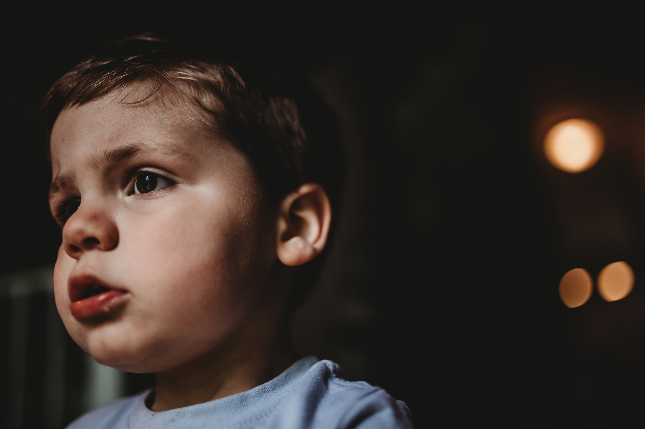 Profile photo of little boy standing near front door light