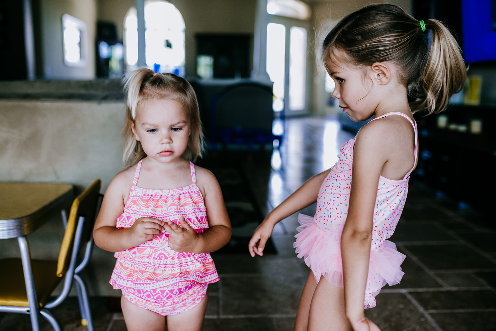 Sisters in their pink bathing suits wait to go in the pool