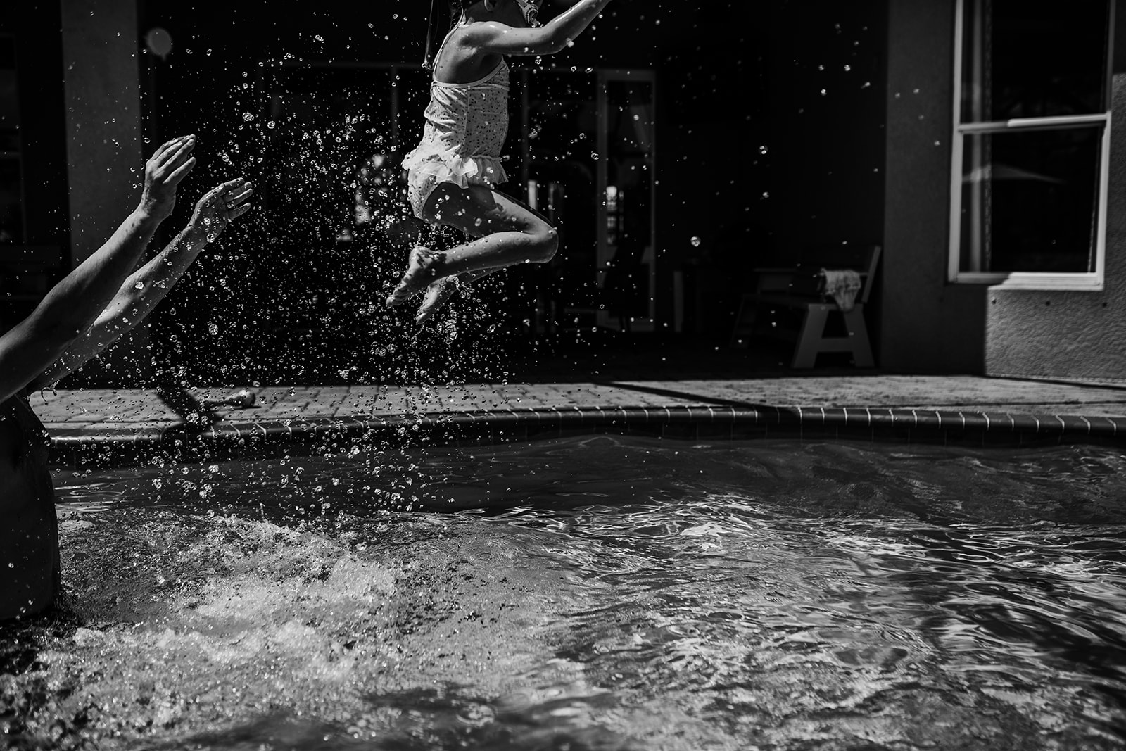 dad throws daughter in the air in the pool