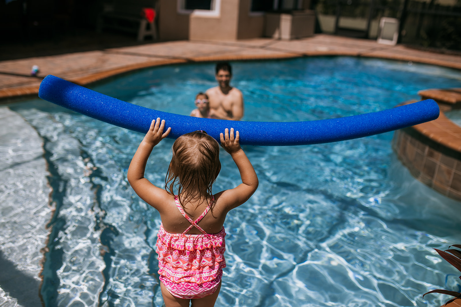 Toddler holds pool noodle as sister and father watch in the pool