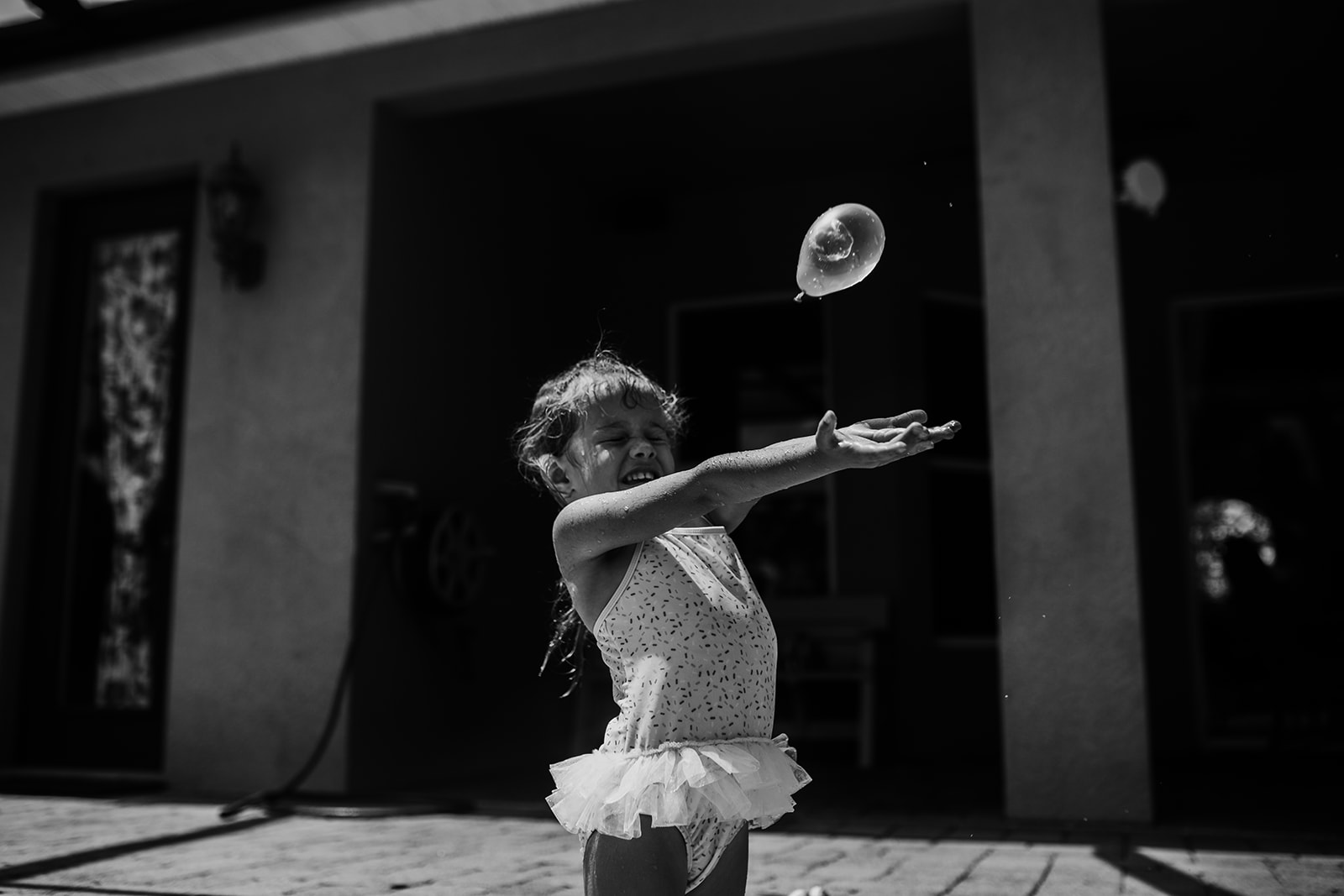 Little girl reaches her arms out to catch water balloon thrown at her