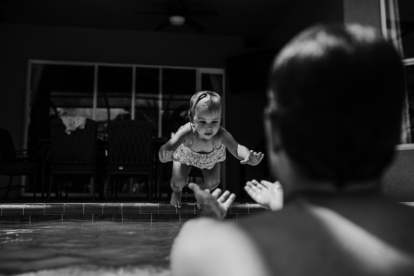 Little girl jumps in the pool towards dad