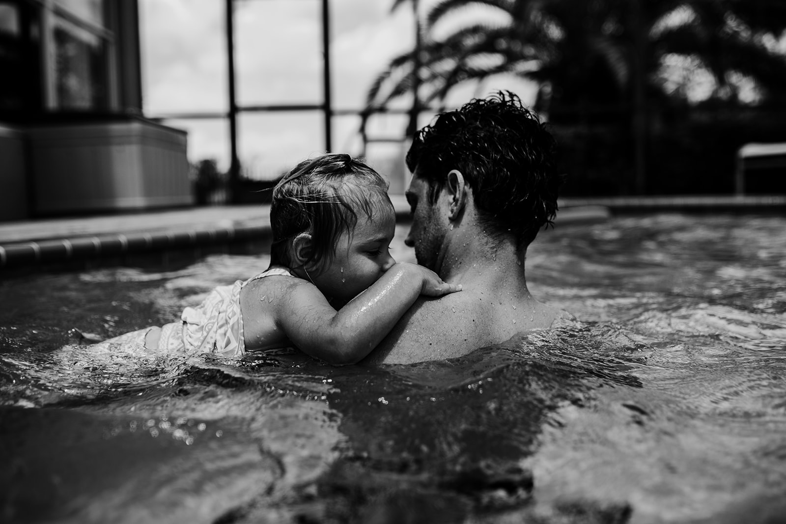 Little girl cuddles with father in pool