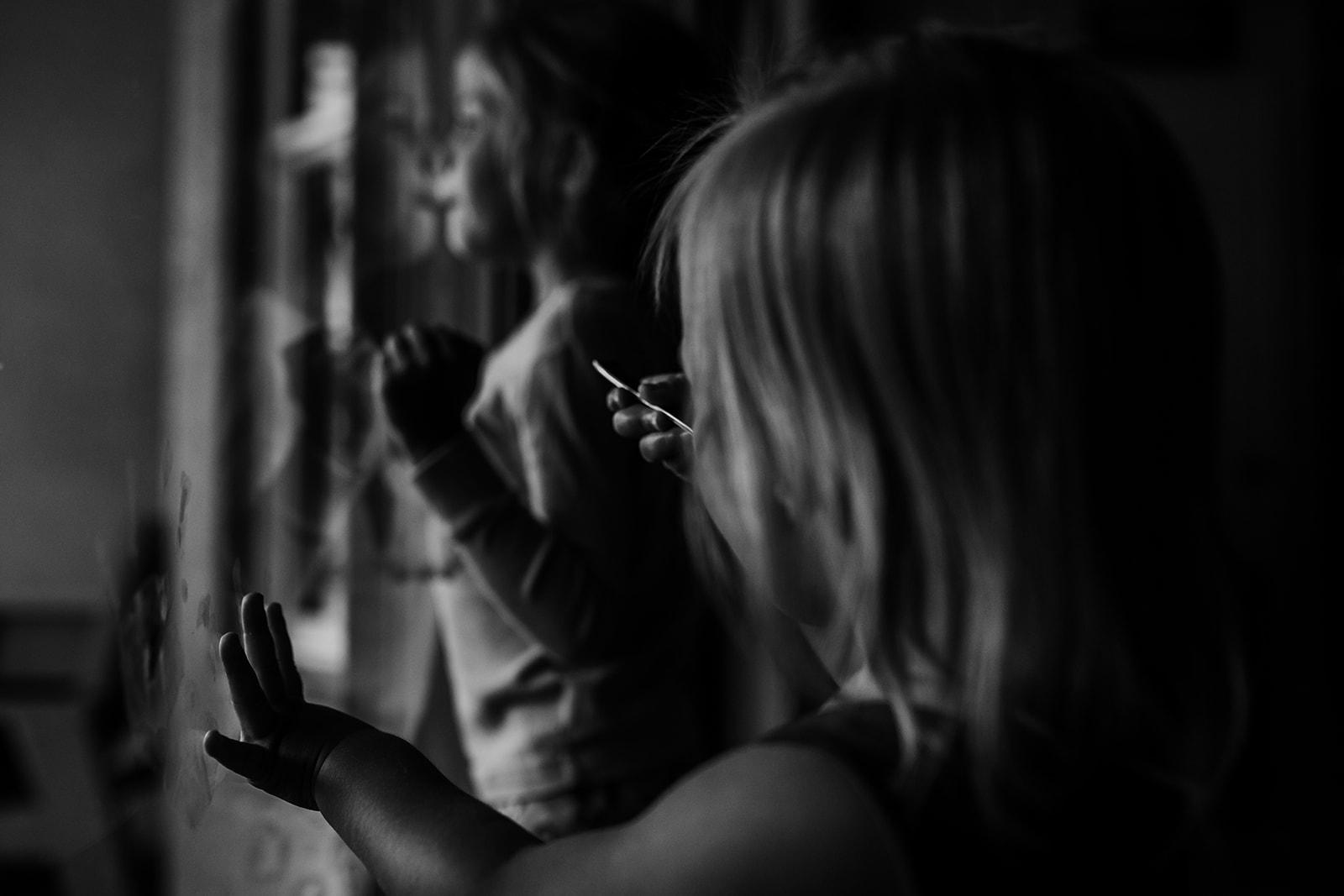 Little girls look outside sliding glass doors