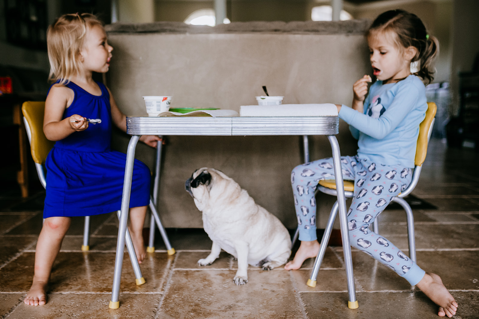 Sisters eat lunch at their kid's table while pug waits underneath for scraps