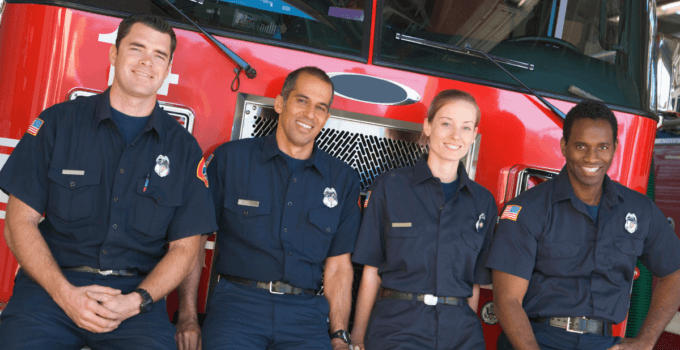 Happy-Firefighters-Leaning-Against-Front-of-Fire-Truck-680x350.png