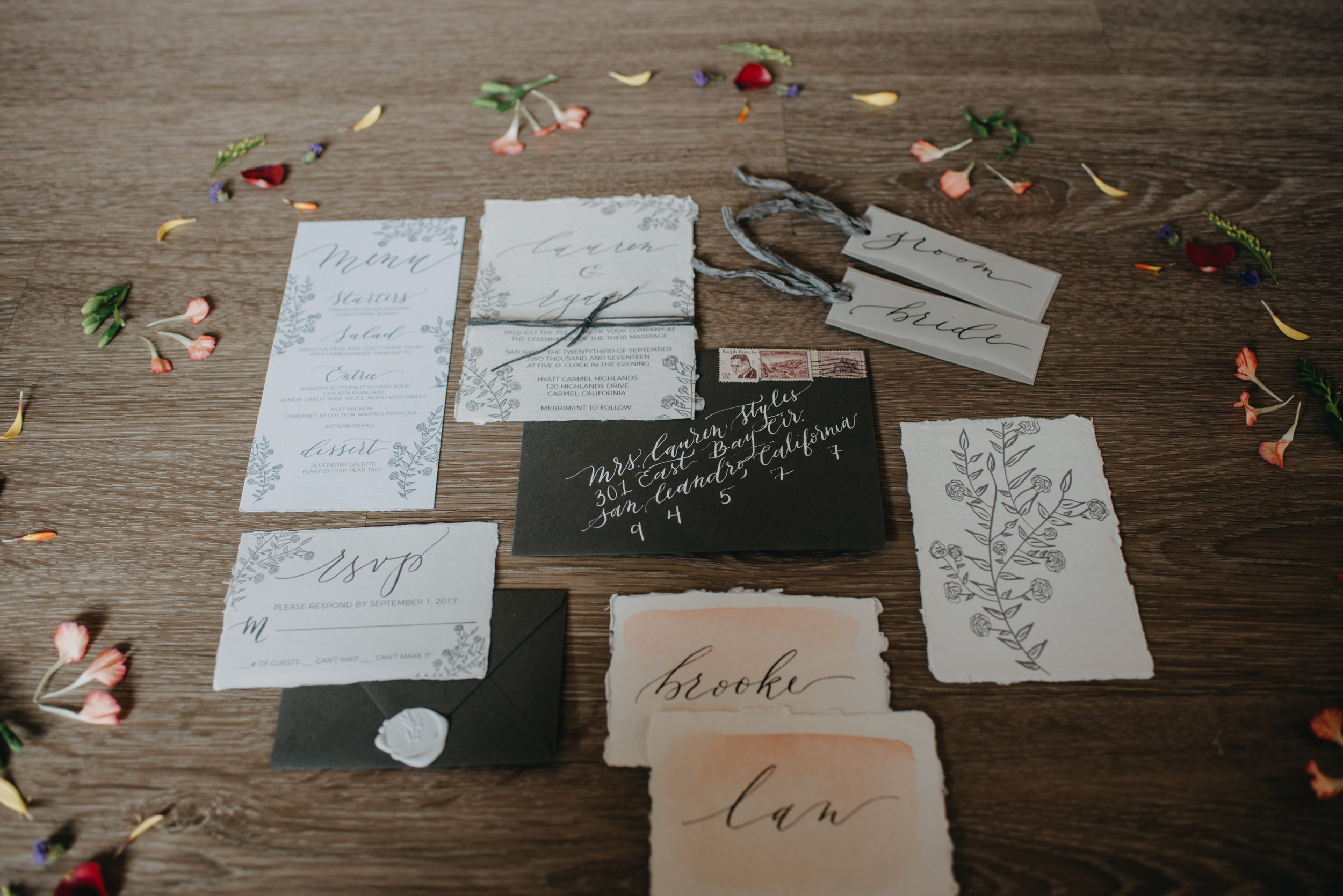 dried flowers and handwritten wedding invitations