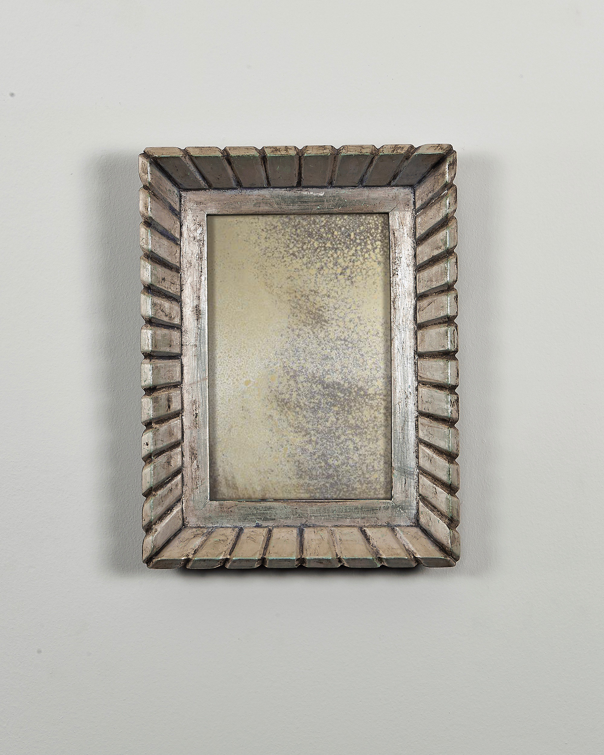 antiqued mirror in custom carved gilded frame