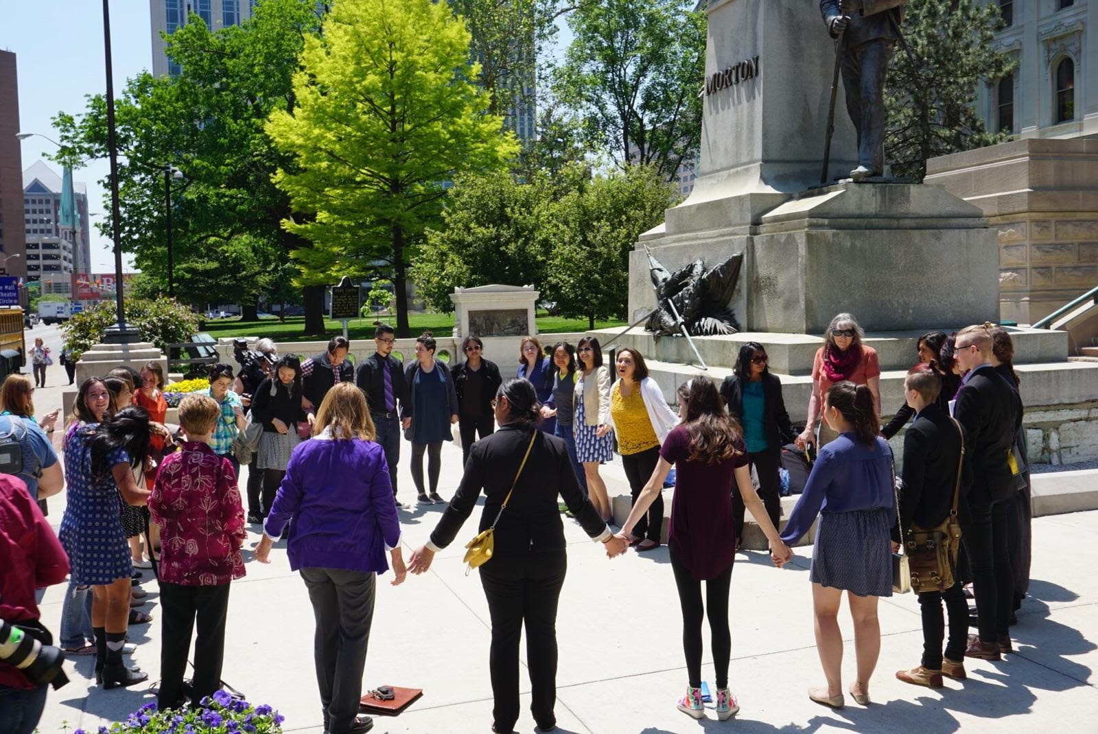 A circle of activists hold hands in front of the Indiana State Capitol to show solidarity with Purvi Patel.