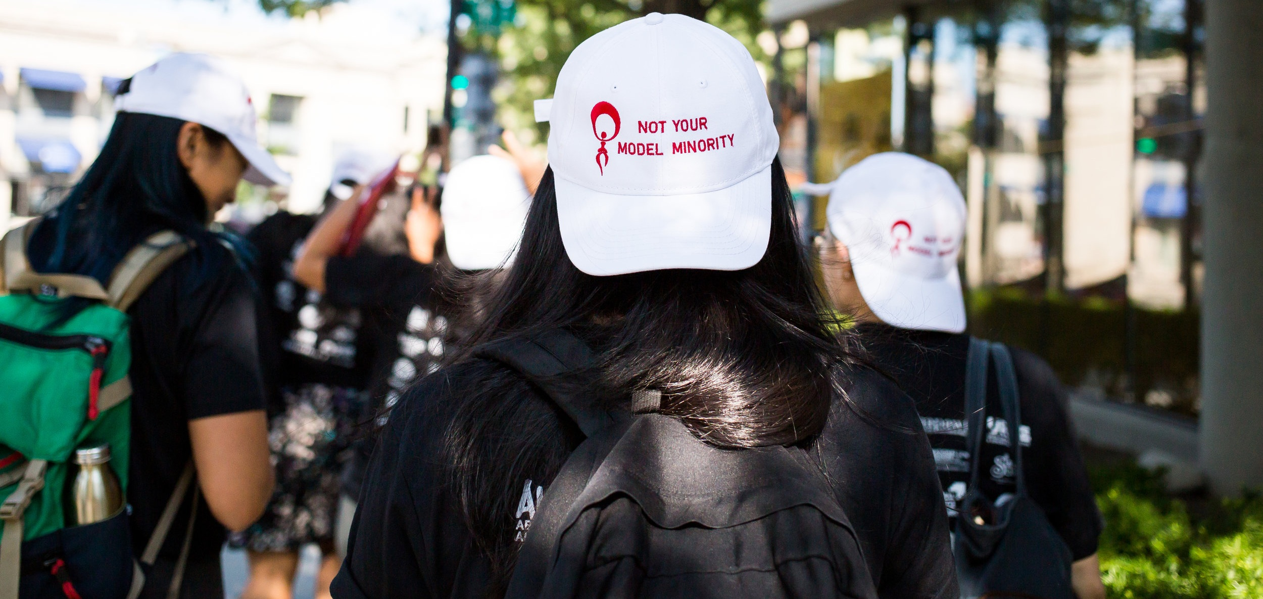 "A woman with flowing black hair is wearing a cap that reads ""NOT YOUR MODEL MINORITY."" The cap is worn backwards, and several other people are wearing the same hat in the background."