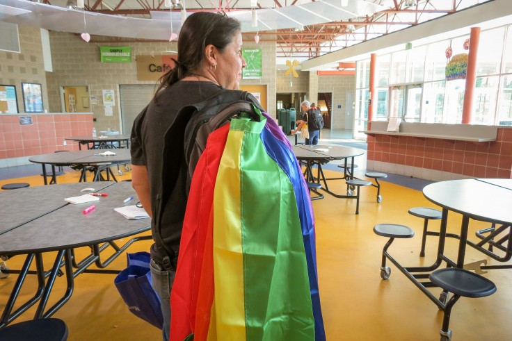 Sara McDonald, director of operations at conference sponsor CU Boulder's School of  Education, sports a rainbow flag. - Jenny Brundin/CPR News