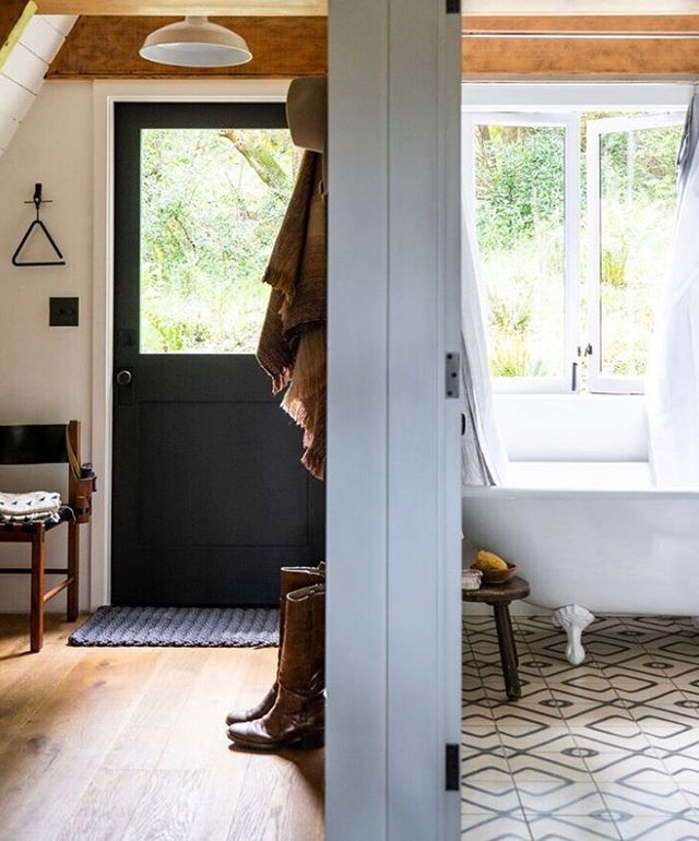 both the mud room + bathtub look out onto the back deck surrounded by wild huckleberry, ferns, coffee berry + bay trees 🌿💚.. I love that my ever present boots + my grandfather's binoculars are in this photo by Tom Story @sunsetphoto .. design by me @blythedesignco ..tile @communedesign for @exquisitesurfaces ..door hardware +bath tub @rejuvenation .. vintage factory light @stuffsf .. metal triangle @schoolhouse