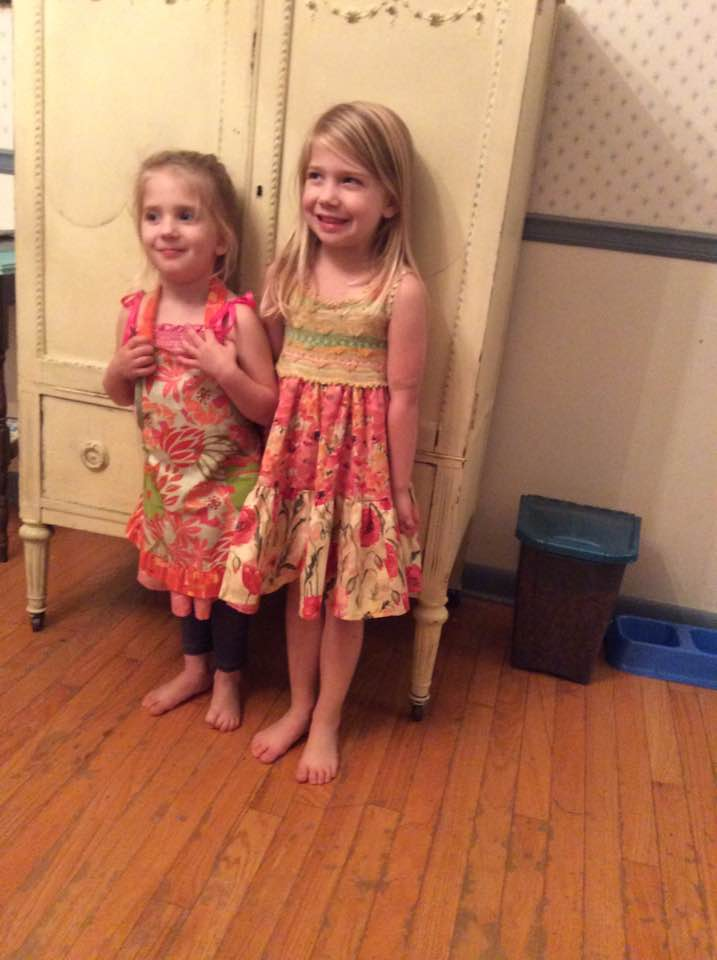 My great nieces wearing the apron and dress I made them. I hand-knit the bodice of the dress.