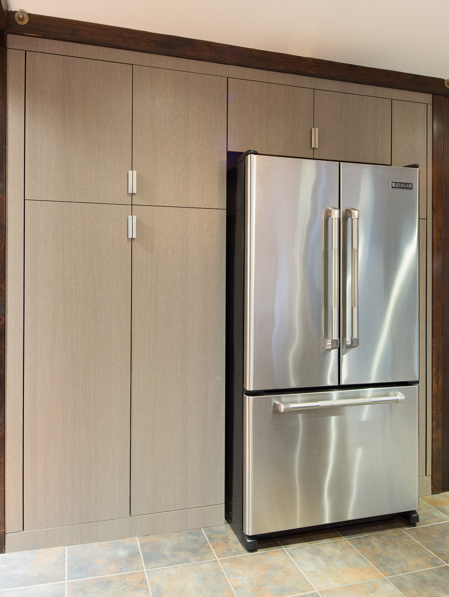 Custom kitchen cabinetry surrounding a refrigerator in grey oak Shinoki