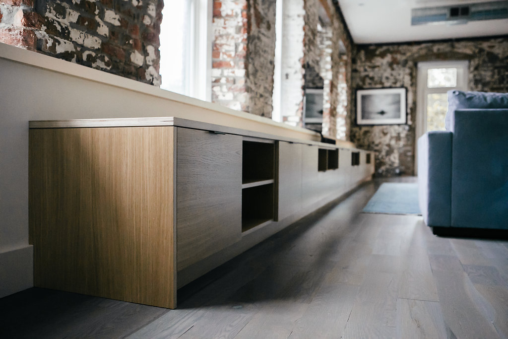 Long and low built-in media storage and bench in white oak veneer on Baltic birch plywood