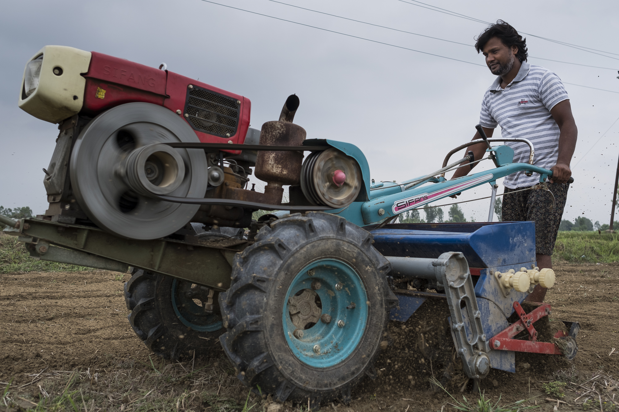 Ajeet Karma uses his two wheeled tractor to til his land planting seed and fertiliser at the same time.