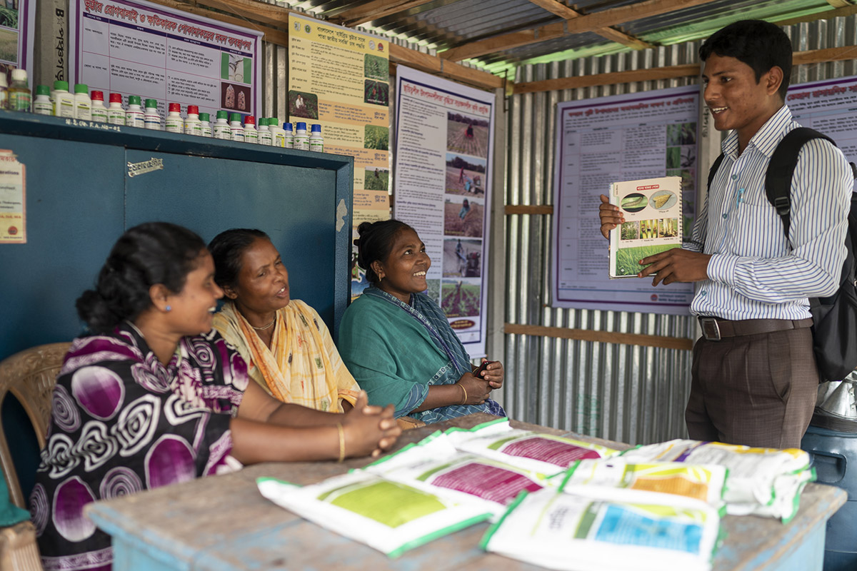 Kalpana and other farmers sit inside a small agro-input shop and listen to a representative from ACI, an agri-input company working across Bangladesh.