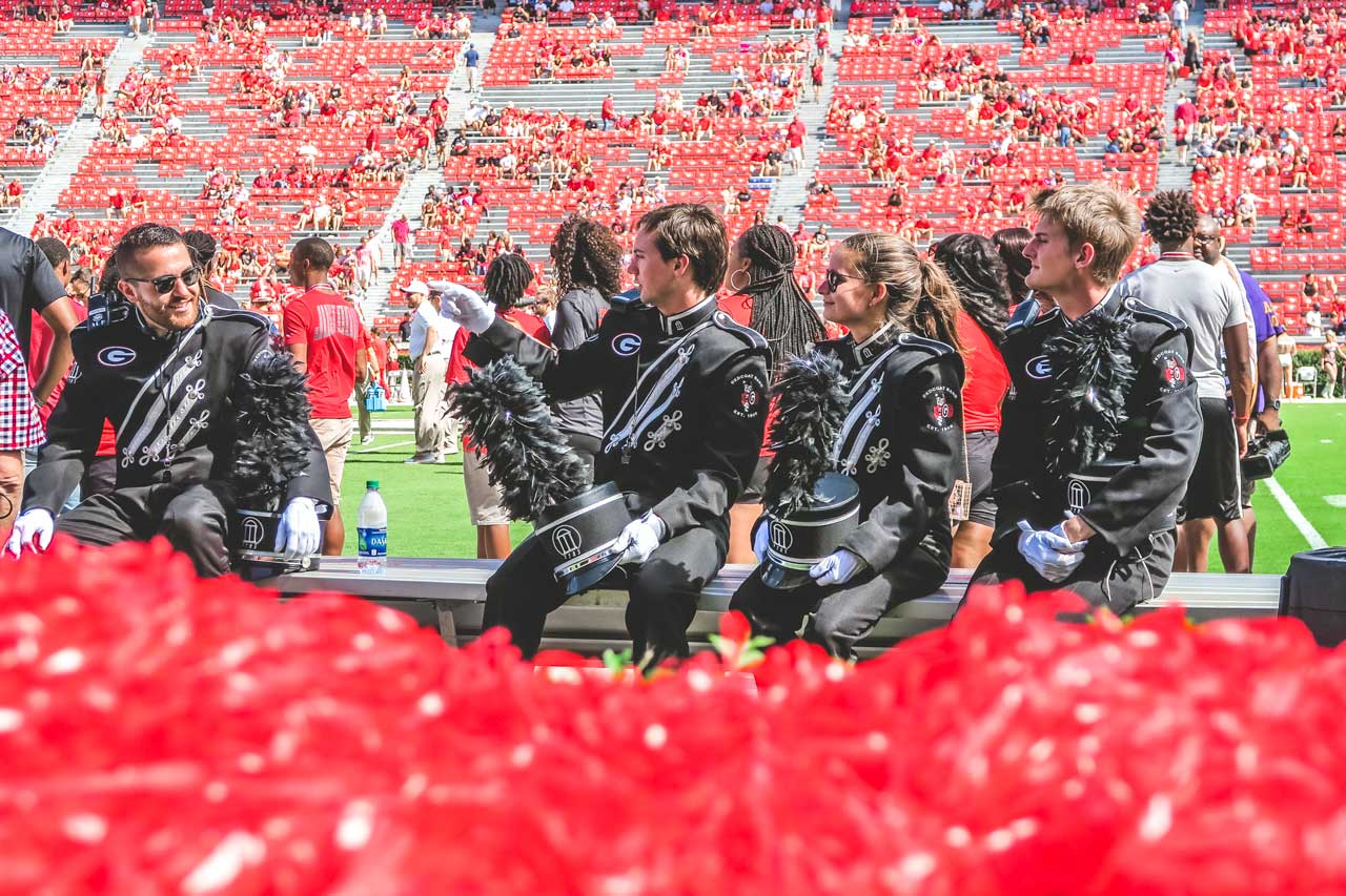 Three members of the Redcoats relax during pregame of UGA vs MTSU