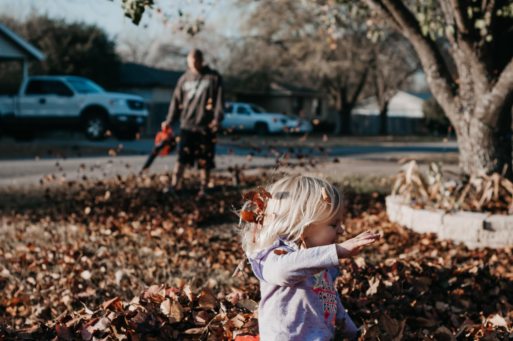 lifestyle photograph of a young girl playing in leaves