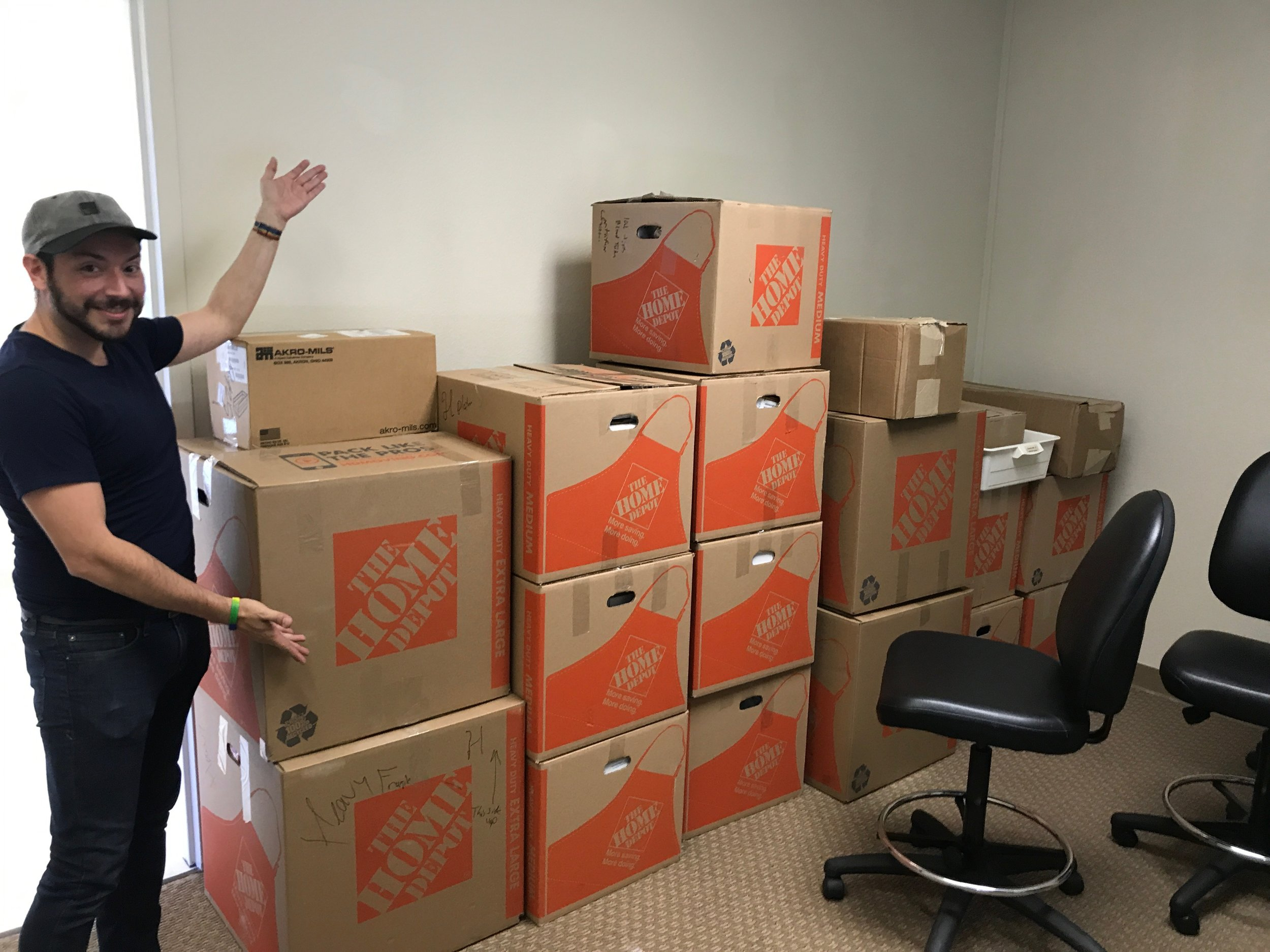 Jesse Cortez, PhD shows off some of the many boxes of supplies at our new location.