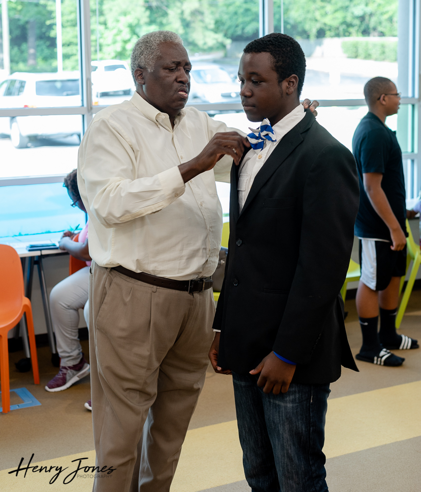 Brother Marion Wright helping Marcellus Charles Lewis with his bowtie.