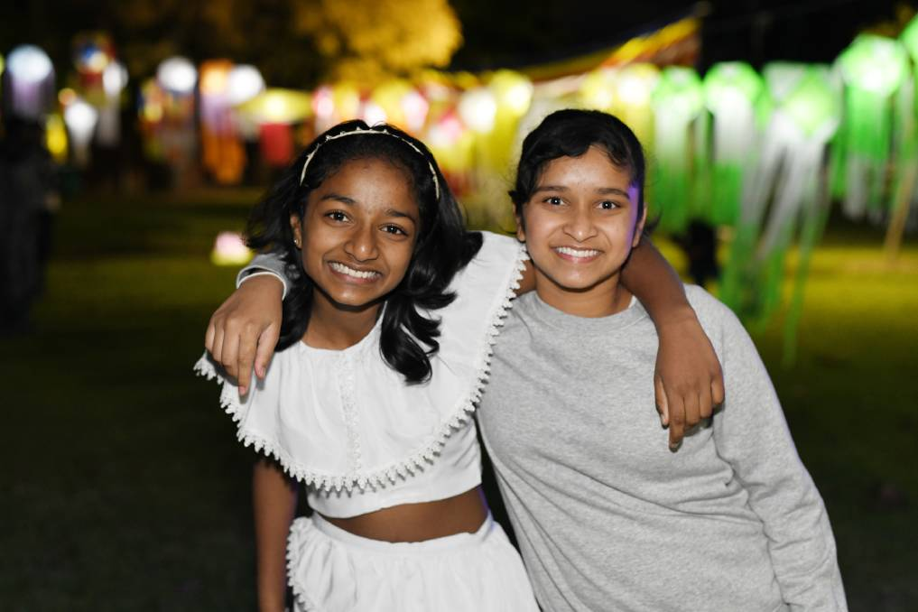 """ALL SMILES: Dinara Piyasiri, 12, and Nethukee Jayasekera, 11, enjoy celebrating Vesak together.    Wagga's Buddhist community united to light lanterns and commemorate one of the most significant days in their religious calendar. Wagga Sri Lankan Community Association and the Potowa Buddhist Group celebrated Vesak on Sunday. """"Buddha was born on this day, he attained enlightenment on the same date and he passed away on the same date again,'"""