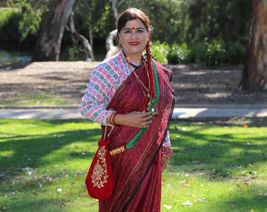"""REPRESENTING NEPAL: Geeta Parajuli says she is proud of her heritage and the traditional dress that reminds her of Nepal's rich history. Picture: Les Smith    Although a proud Australian, one Nepalese woman holds her heritage close to her heart.    Over the coming weeks, The Daily Advertiser will highlight fashions from cultures that are thriving in Wagga, with women leading the way forward.    Geeta Parajuli said the traditional Nepali dress is the sari and chaubandi cholo.    """"The sari is a five-metre long material that is folded into plaits and tucked into a long skirt with no plaits in it that we wear underneath to hold the material in place,"""" she said. """"The sari is wrapped in such a way to fit bodies of any size. Cholos and saris could be made out of any fabric, but Dhaka is unique to Nepal.""""    Ms Parajuli said she came to Australia to ensure her child received the best education. """"Though I am an Australian citizen, Nepal is always in my heart,"""" she said. """"I have lived here about 15 years, so I love Australia equally. I always love to wear our cultural costume to represent my country.""""    Ms Parajuli said her dress is made out of the original fabric that forms the basis of one of the most important small industries in Nepal.""""Chaubandi means closed in four points and there are no buttons,"""" she said.""""Dhaka is a hand-woven fabric and the national hat, called topi, for men is also made out of the same material.    """"Palpali Dhaka is woven in the Palpa district of western Nepal and is very famous and provides employment to the local community."""" As well as the fabrics, there is a range of accessories used to add colour and signify relationship status in Nepalese culture.On example is the choora, the glass bangles and all gold jewellery is 24-carat. """"The red on my hair partition is called sindoor, which is a sign of being married,"""" Ms Parajuli said. """"We also put a red tika on [the] forehead. """"The golden necklace is called potey, the bunch of beads are called tilahari,"""