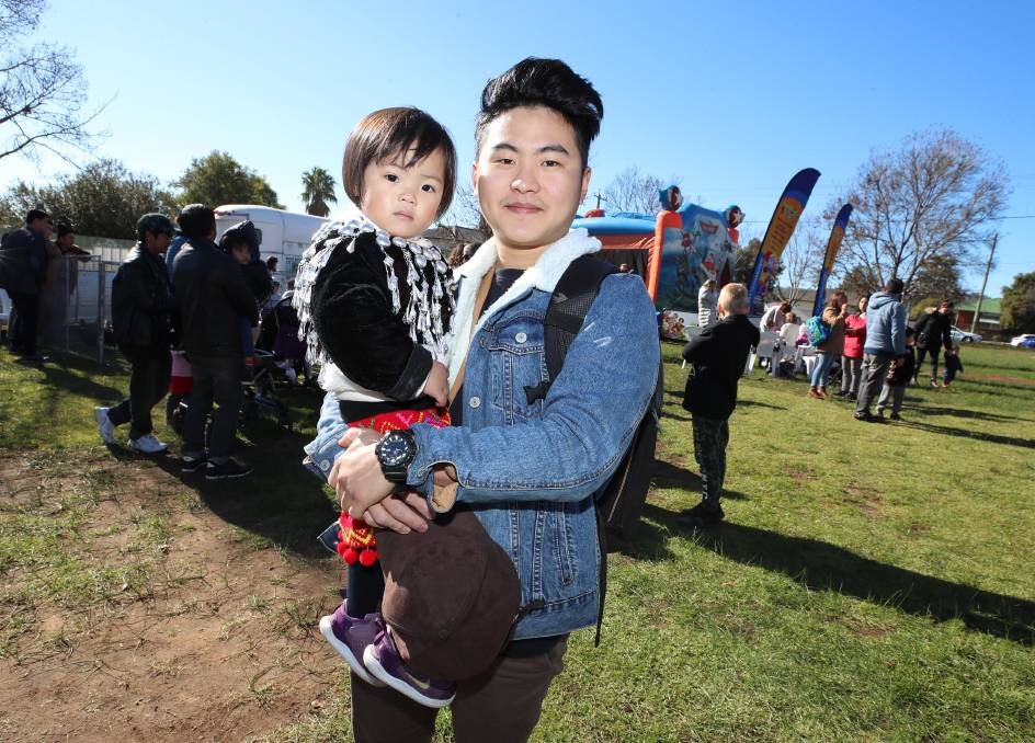 """Phong Tiwangce with his sister Grace Tiwangce, 2, at the Refugee Week Family Fun Day. Picture: Les Smith   FORCED to flee his home country to survive, one Burmese refugee says he has been welcomed into the Wagga community. During the weekend's Refugee Week community celebration at Henschke Primary School, Phong Tiwangce told of how he arrived in the city when he was 12 years old. """"My mum and dad and I had to flee Burma because we feared for our lives,"""" he said."""