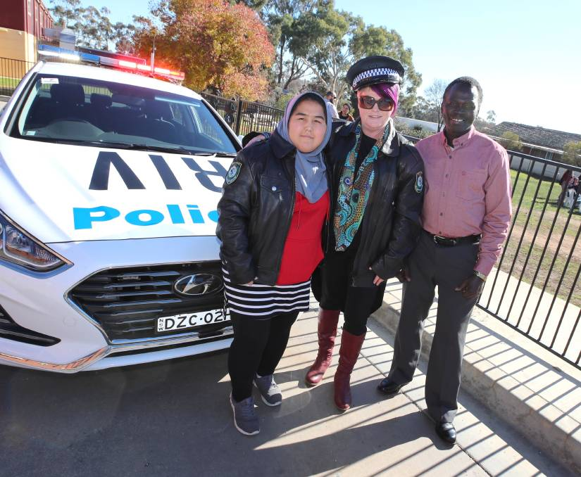 """DRESS UP: Fatema Rahimi, Belinda Crain and Samson Abbas take a happy snap with police gear and car at the Refugee Week Fair. Picture: Les Smith   """"It brings everyone from the community together and is a celebration of those here with a refugee background and what they contribute,"""" she said. """"Looking around it's great to see so many people here from Australian-born to our refugees.""""    Ms Crain thanked Wagga Council, Multicultural Council NSW, Teys and Rotary for funding and donating time and food."""