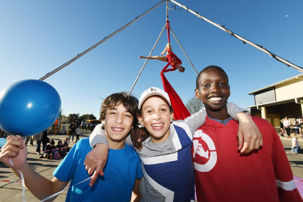 """GOOD TIME: Kristen Ho (background), Mohamed Ghazy, 11, Yousef El Sanabary, 12, and Bol Lual, 13, all having a wonderful time at the fete.  IT was a display of all-things multiculturalism today when the Wagga community came together at Wagga Christian College's fete and fireworks display. Among the fun were rides, games, food, dancing and music from various cultures. Traditional fete stalls - including craft, garden and books - also ensured all attendees were kept entertained. College principal Phillip Wilson said the event is run every second year and multiculturalism is this year's theme.  """"We're aware that about 20 per cent of our population comes from other countries, so we deliberately set out to have participants do cooking, exhibitions or performances to celebrate their cultures,"""" Mr Wilson said."""