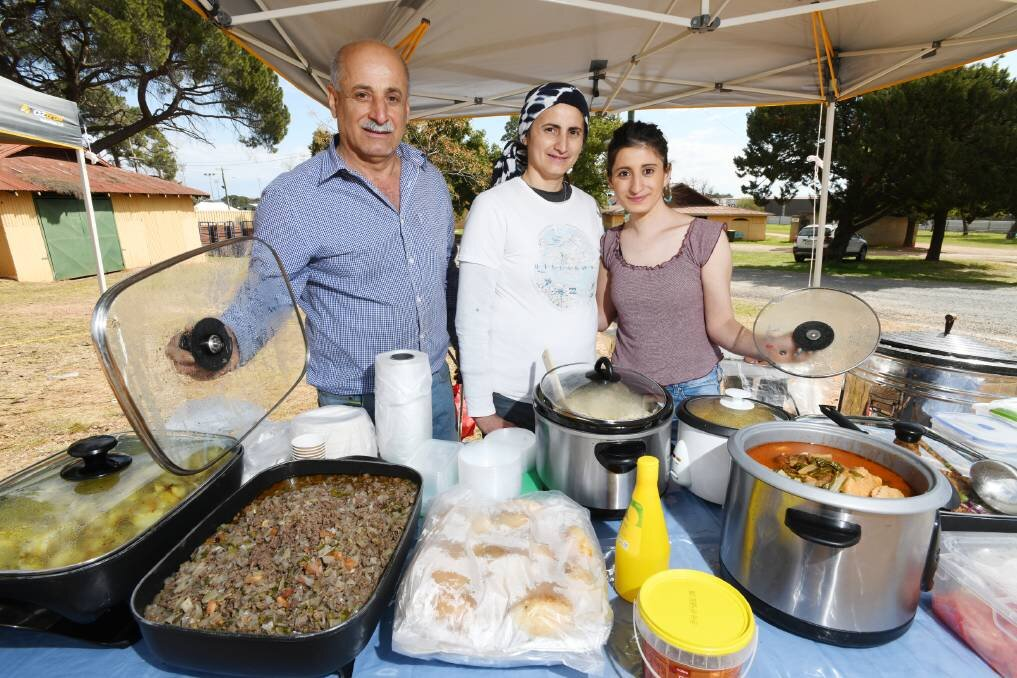 """TASTE OF HOME: Kamal Gundor, Nazi Perabo and Diyana Gundor at their food stall at the Riverina Producers' Market.    Utilising the powerful language of food, one Yazidi family have built a life for themselves in Wagga.It's almost that time of year where residents and visitors can eat dishes from around the world to their heart's content. In the spirit of the upcoming Fusion Festival,  The Daily Advertiser  is profiling some of the delicious cuisines that can be found in this city, and the people who can cook them with their eyes closed. Diyana Gundor and her family arrived as refugees to Wagga in 2017 as part of a wave of Yazidi refugees to arrive in Australia following a campaign of genocide by ISIS in Northern Iraq. An avid cook, Ms Gundor built her confidence to the point where she was able to open a food stall at the weekly Riverina Producer's Market, selling their traditional flatbread among other dishes. """"We make the bread with flour and yeast and salt and leave it for one day,"""" she said.""""After that, we roll it out and put in the oven.""""Ms Gundor and her loved ones had to flee their homes as the Yazidi people were being murdered. """"My family wasn't safe in Iraq,"""" she said. """"Lots of our family and friends were killed by ISIS. """"It is great living in Australia, and I love it here, thank you so much to everyone.""""On the menu at their stall is often Middle Eastern chicken, dolma, chickpea soup and other delicious, traditional dishes.    Belinda Crain, CEO of the Multicultural Council, said Ms Yamak is just one of the community members who they have helped to set up a business at the Riverina Producers' Market that runs every Thursday at the Wagga Showgrounds."""