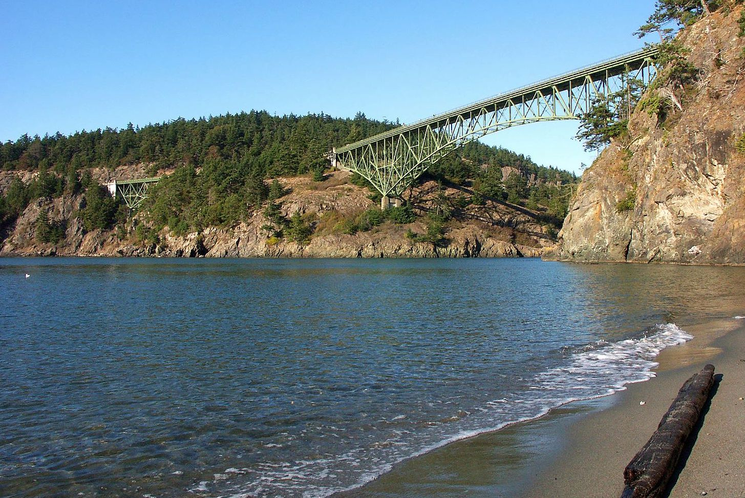 Water and a beach with a view of trees and rocks and a bridge in the distance