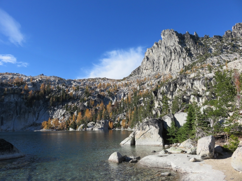 An alpine lake next to a dirt rock lined trail. Granite mountains in the distance with green and yellow trees against a blue sky.