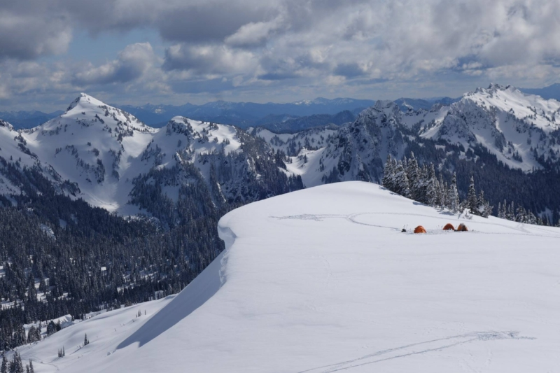 A small group of tents on snow. Snow covered mountains and trees in the background.