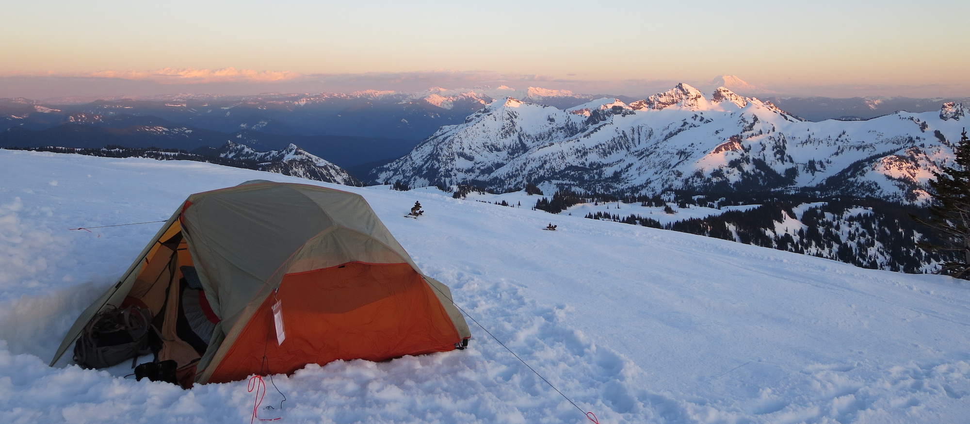 Tent on snow at sunset with snow-covered mountains in the background.