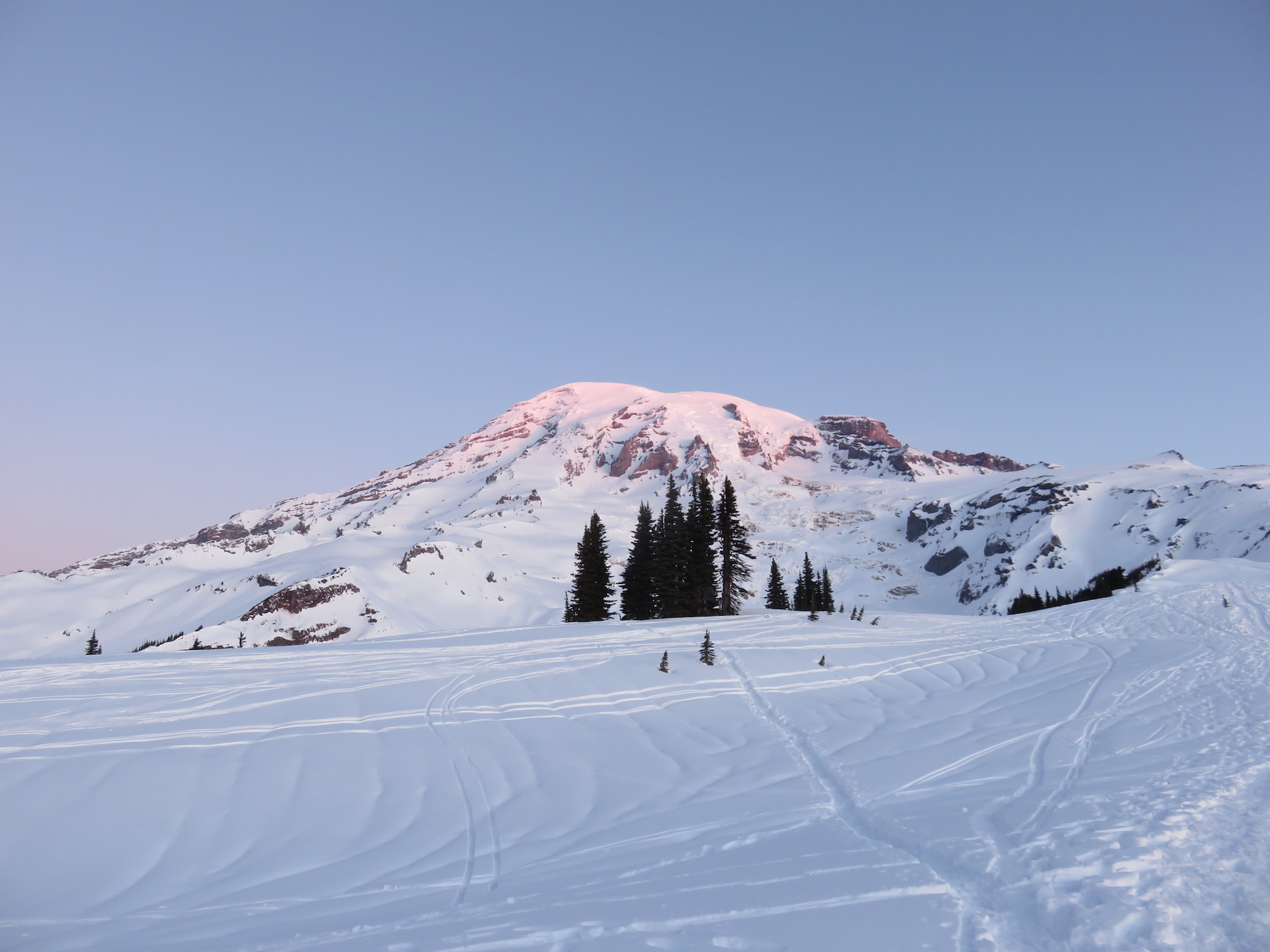 Sunrise light glows pink on the top of a snow covered mountain.