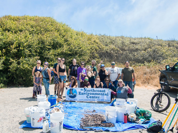 A group poses for a photo with a Northcoast Environmental Banner after a beach cleanup. In front of the group is a tarp and buckets with all the trash they collected.