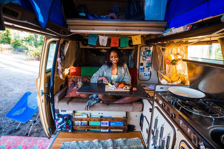 Noami sites in her van chopping veggies on a cutting board.