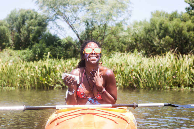 Noami sits in a canoe on the water and applies a natural sunscreen to her face.