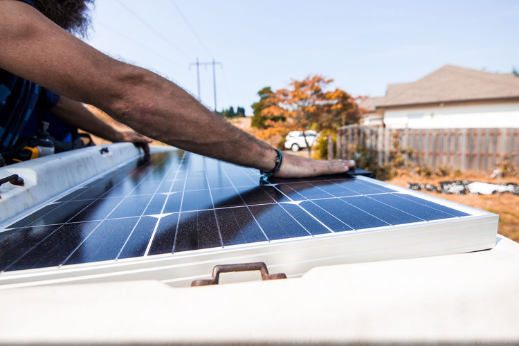 Dustin adjusts a solar panel on the roof of his van.