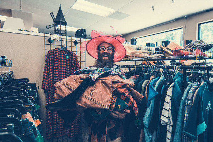 Dustin stands in the aisle of a thrift store holding an armload of clothes while wearing a large pink hat with a bow on top.