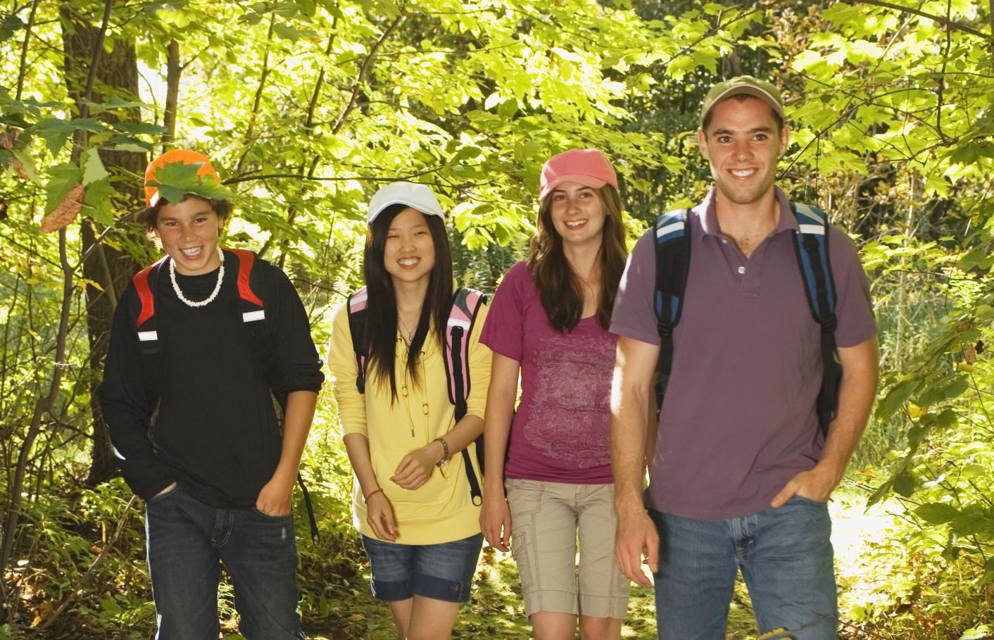 Teenagers hiking through sunny trees