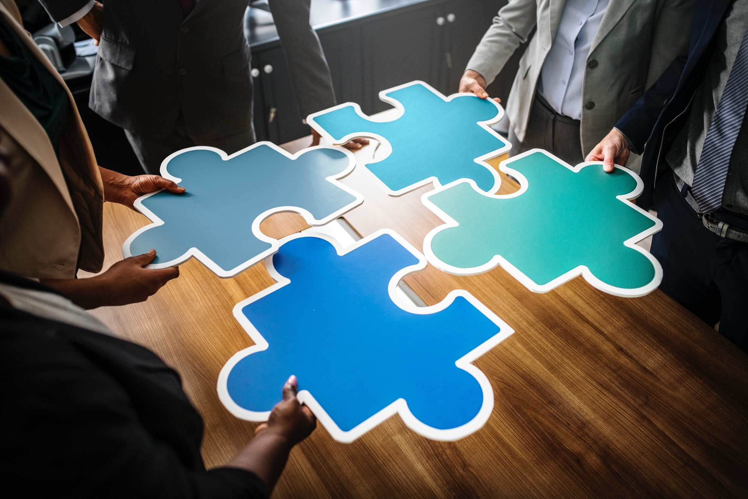 People in office setting holding up giant puzzle pieces that fit together