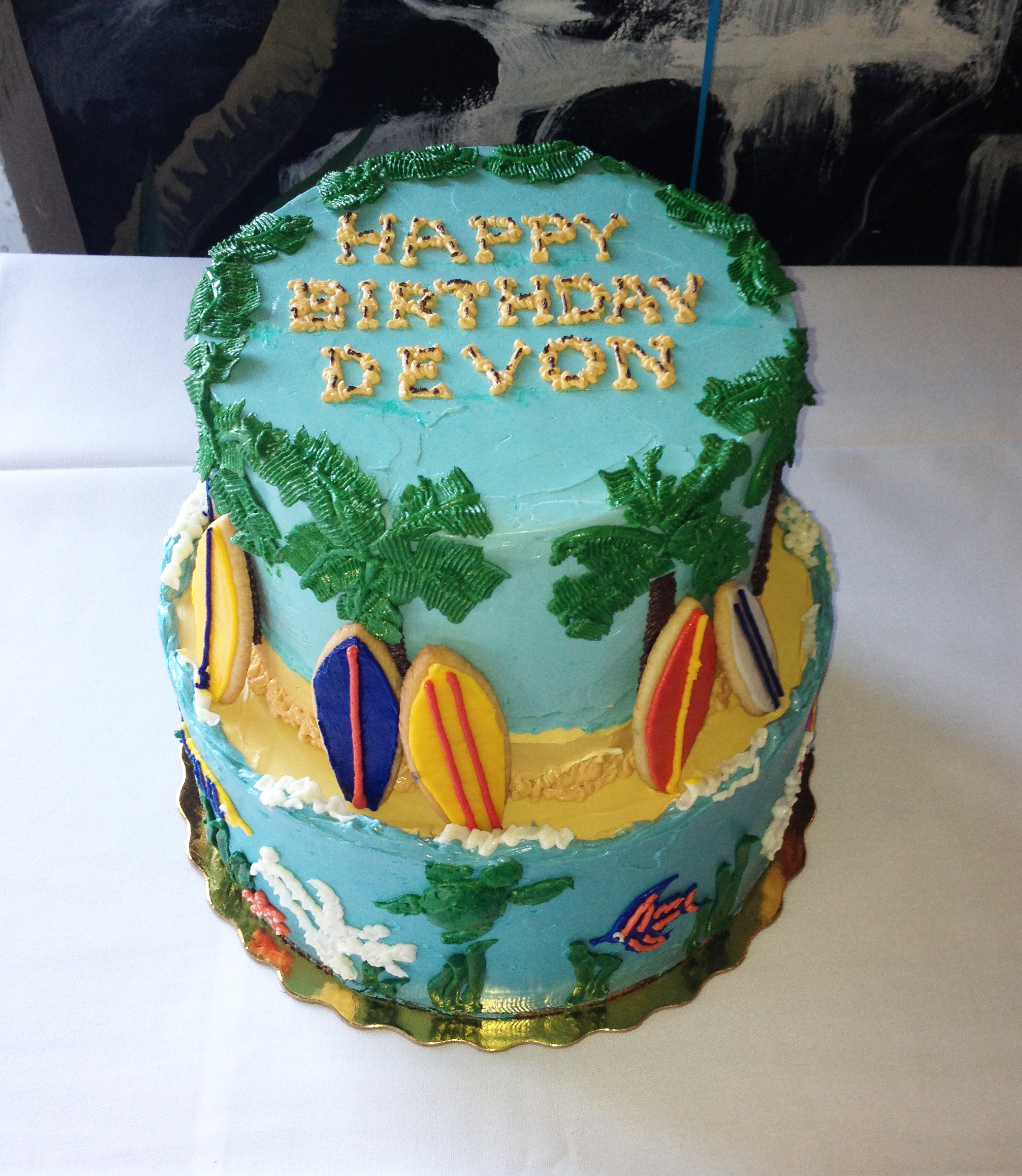 A Hawaiian-themed party demands a cake with complete with cookie surfboards.
