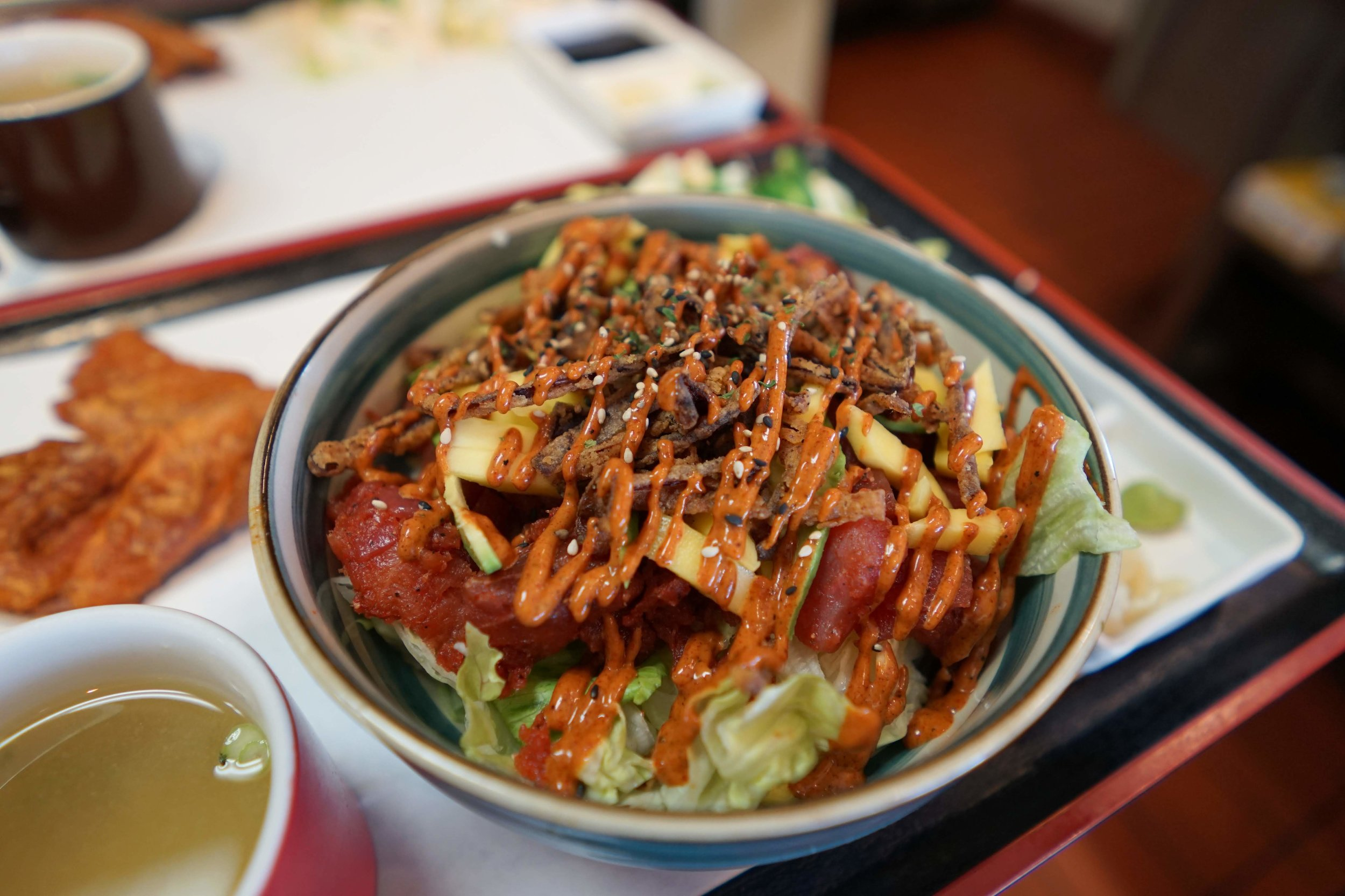 Make Your Own Bowl with spicy tuna, avocado, mango, crispy fried onions, and spicy mayo. Served over salad.